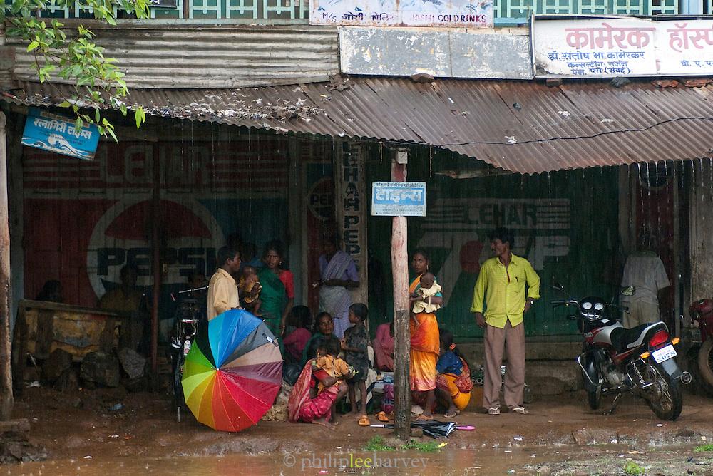 Locals shelter under corrugated iron roof during monsoon rains, Goa, India.