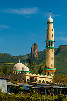 """Minaret of a mosque, near Gondar, Ethiopia. In the background is a rock formation called """"The Devils Nose (or Tikil Dingay)""""."""