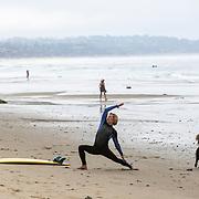A surfer does yoga on the beach in Malibu.