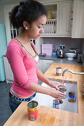 Teenage girl rinsing out tins at kitchen sink before putting them out for recycling,