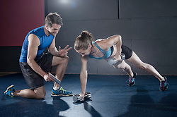 Fitness instructor giving training to client in the gym, Bavaria, Germany