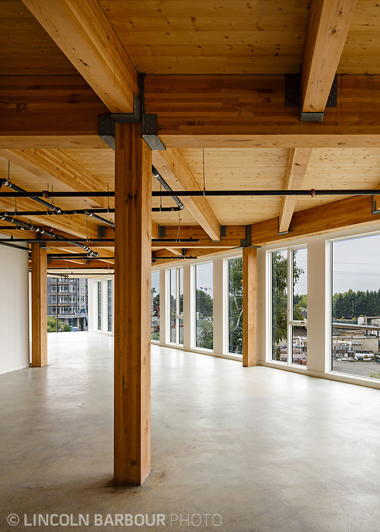 An empty commercial space with a raw, industrial look and feel featuring concrete floors, exposed wood, and floor to ceiling windows with an incredible view. Architectural photograph of the Flatiron building designed by Works Progress Architecture