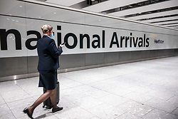© Licensed to London News Pictures. 17/01/2021. London, UK. A cabin crew member arrives at London Heathrow. Passengers arriving from abroad on Monday morning will have to show that they have had a negative Covid-19 test. Today, Foreign Secretary Dominic Rabb, said that lockdown could be lifted in March but with tier systems in place as health chiefs reveal that a 24/7 vaccination pilot will begin next week as total Covid-19 deaths reach over 88,000 this weekend. Photo credit: Alex Lentati/LNP