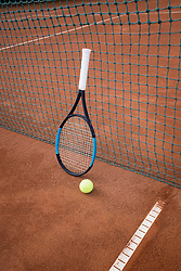 Tennis ball with racket leaning on net of tennis court, Bavaria, Germany