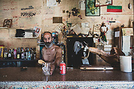 The owner of the Elvis Bar serves a Coke with ice to his first customer of the day, a passing photographer-pilgrim, in the small town of Reliegos, Spain. The Elvis Bar is a somewhat famous stopping point for many pilgrims on the Camino. (June 21, 2018)<br />