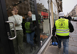 19 January 2019. Paris, France.<br /> Gilets Jaunes - Acte X take to the streets of Paris. Shop workers watch the march from behind locked doors. An estimated 7,000 people took part in the looping 14 km route from Place des Invalides to protest tax hikes from the Government of Emmanuel Macron imposed on the people. An estimated 80,000 people took part in protests across the country. Regrettably the movement has attracted a violent element of agitators who often face off with riot police at the end of the marches which tends to deflect attention away from the message of the vast majority of peaceful protesters.<br /> Photo©; Charlie Varley/varleypix.com