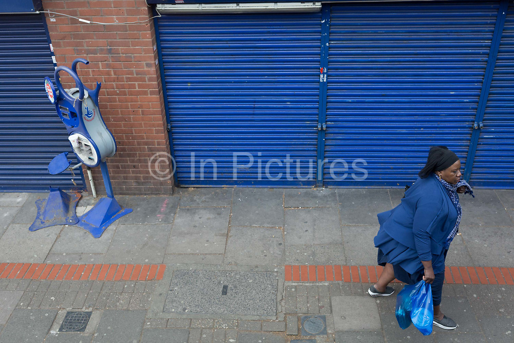A woman in blue walks past blue shutters and a broken National Lottery ticket dispenser on the Walworth Road, on 23rd March 2019, in London, England.