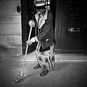 Paris - Place des Vosges - Juin 2012 - Femme balayant la porte d'une habitation.
