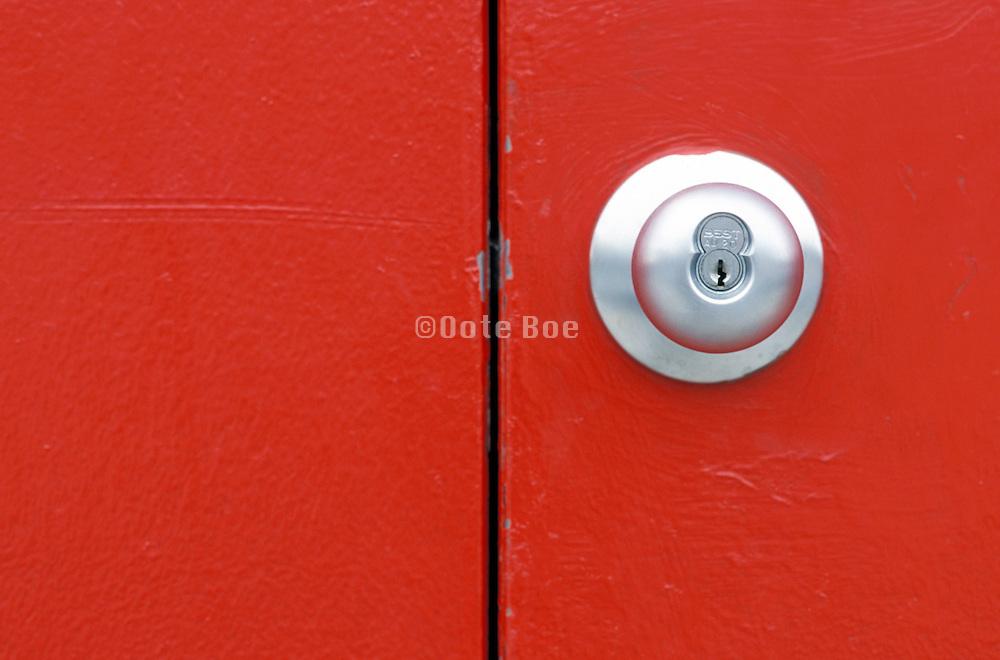 doorknob and keyhole on red metal door
