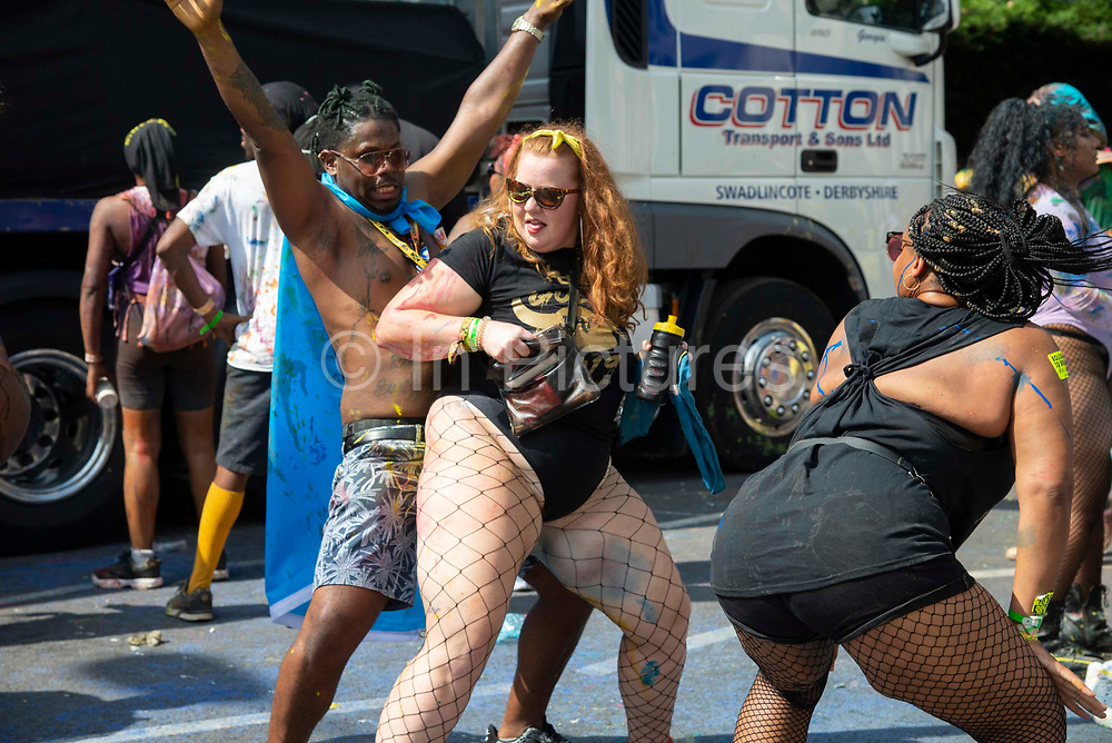Party goers take part in the traditional Jouvert opening parade of the Notting Hill Carnival, where paint is thrown and they cover each other in chocolate and flour on 25th August, 2019 in London, United Kingdom. One million people are expected on the streets in scorching temperatures for the Notting Hill Carnival, Europes largest street party and a celebration of Caribbean traditions.