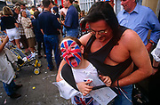 A young boy with a Union Jack painted on his face enjoys the community spirit of a street party during 50th anniversary celebrations of wartime VE day. Along with neighbours and family, the lad shouts out while being tickled as his neighbourhood celebrates the 50th anniversary of VE (Victory in Europe) Day on 6th May 1995. In the week near the anniversary date of May 8, 1945, when the World War II Allies formally accepted the unconditional surrender of the armed forces of Germany and peace was announced to tumultuous crowds across European cities, the British still go out of their way to honour those sacrificed and the realisation that peace was once again achieved. Street parties now – as they did in 1945 – played a large part in the country's patriotic well-being.