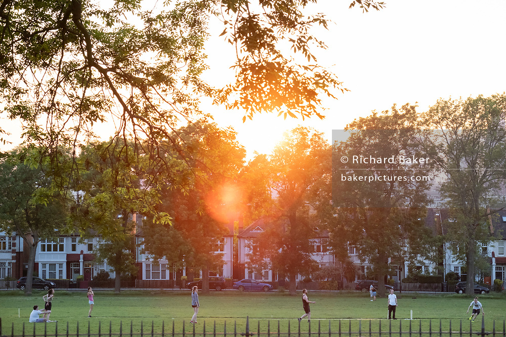 With a setting sun sinking below a line of homes and ash trees, a group of friends play a game of informal cricket in Ruskin Park, a public green space in Lambeth, south London, on 13th June 2021, in London, Englnd.