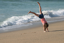 A young girl turning cartwheels on Fistral Beach in Newquay, Cornwall.