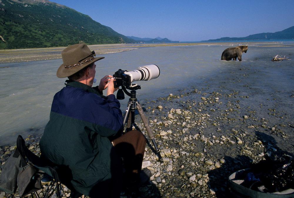 Alaska. Katmai NP. Kukak Bay. Photographer Ron Phillips changing film while working a brown bear.