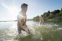 Mature couple splashing water to each other on lake, Bavaria, Germany