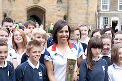 © London News Pictures. 17/07/2012. Tonbridge Castle, Tonbridge, Kent. Dame Kelly Holmes poses with the Olympic Torch with children from her old school, Hugh Christie School in Kent, with the Olympic Torch in the gardens of Tonbridge Castle, Kent.  Photo credit should read Manu Paomeque/LNP.