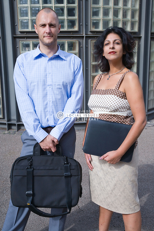 Two adults standing outside their office building,