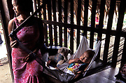 Amy de la Cruz, 16 rocks to sleep her 6 month old daughter, Rose Ann. In their house along Feeder Rd. in the village of Busok Busok, Aurora province, Philippines