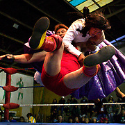 Cholita Yolanda La Amorosa fighting with Barba Negra during the 'Titans of the Ring' wrestling group performance at El Alto's Multifunctional Centre. Bolivia. The wrestling group includes the fighting Cholitas, a group of Indigenous Female Lucha Libra wrestlers who fight the men as well as each other for just a few dollars appearance money. El Alto, Bolivia, 24th January 2010. Photo Tim Clayton