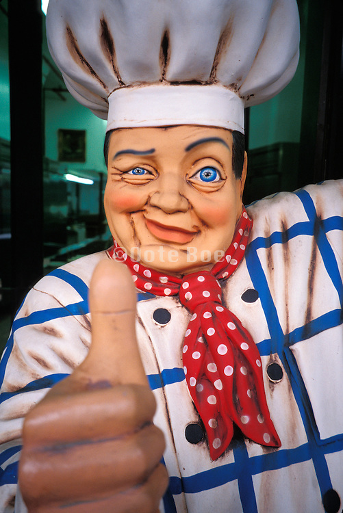 carved figure of chef with thumb up