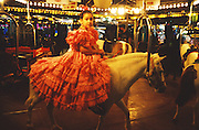 """The Fairground is as much a part of the Sevilla's Feria d'Abril. All the fun of the fair. People dressed up in their finery. Girls and women in pretty flamenco dresses, men in costume suits...The Feria de abril de Sevilla, """"Seville April Fair"""" dates back to 1847. During the 1920s, the feria reached its peak and became the spectacle that it is today. It is held in the Andalusian capital of Seville in Spain. The fair generally begins two weeks after the Semana Santa, Easter Holy Week. The fair officially begins at midnight on Monday, and runs six days, ending on the following Sunday. Each day the fiesta begins with the parade of carriages and riders, at midday, carrying Seville's citizens to the bullring, La Real Maestranza...For the duration of the fair, the fairgrounds and a vast area on the far bank of the Guadalquivir River are covered in rows of casetas (individual decorated marquee tents which are temporarily built on the fairground). Some of these casetas belong to the prominent families of Seville, some to groups of friends, clubs, trade associations or political parties. From around nine at night until six or seven the following morning, at first in the streets and later only within each caseta, crowds of people party and dance Sevillanas, traditional Flamenco dances, Sevillan style drinking Jerez sherry, or Manzanilla wine, and eating tapas. Men and women dress up in their finery, the traditional """"traje corto"""" (short jacket, tight trousers and boots) for men and the """"faralaes"""" or """"trajes de flamenca"""" (flamenco style dress) for women. The men traditionally wear hats called """"cordobés""""."""