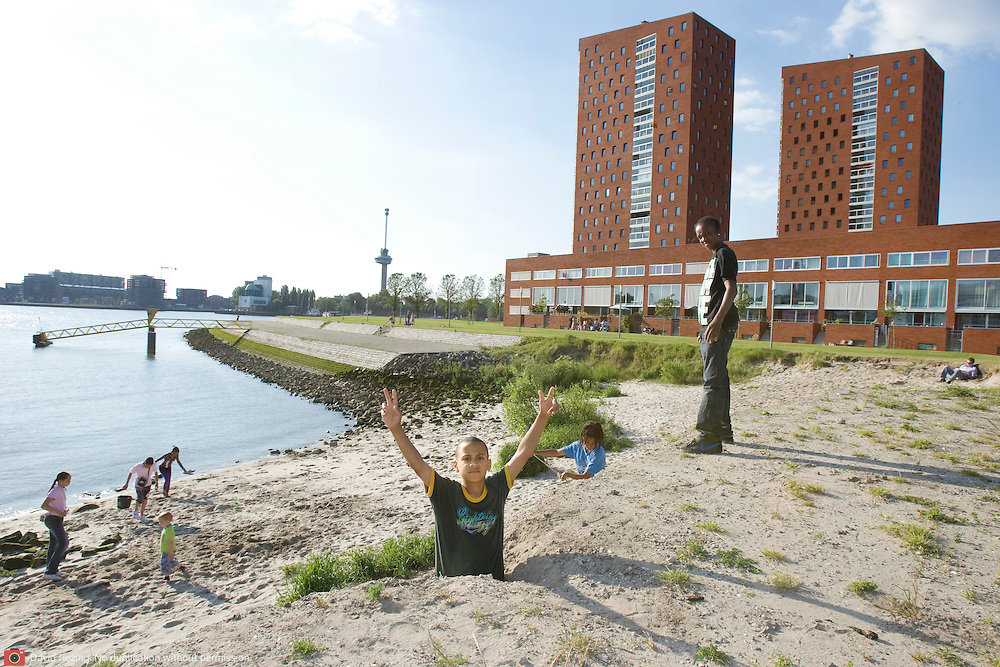 """Nederland Rotterdam 30-05-2009 20090530 Foto: David Rozing ..Nieuwbouw woningen in probleemwijk Katendrecht, kinderen spelen op het strandje aan de rivier de maas, op de achtergrond de nieuwbouw woningen, euromast. Stedelijke vernieuwing, moderne ruime wijk, natuur, natuurlijke oevers, waterveiligheid, ruimte, ruimtelijkheid, kindvriendelijk, speelplaats, speelplek, speelruimte, strand, kindvriendelijke omgeving, buiten spelen, allochtoon, allochtone, kind, jeugd, jongen, fiets, unieke locatie, stads,  New houses / appartments in (former) deprived area / projects """"Katendrecht """" This area is on a list with projects which need help of the government because of degradation in the area etc, youth, , children playing outside, beach, project, suburb, suburbian, problem. Neighboorhood, neighboorhoods, district, city, problems,  daily life Holland, The Netherlands, dutch, Pays Bas, Europe ..Foto: David Rozing/"""