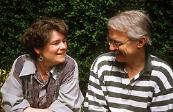 Couple sitting outdoors looking at each other smiling,