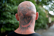 The rear view of a young mans sunburned neck and head that has been tattooed with a roaring tigers head, in south London, on 19th August 2019, in London, England.