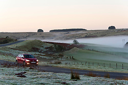 © Licensed to London News Pictures. 26/11/2020.  Builth Wells, Powys, Wales, UK. A car drives through a wintry landscape on the Mynydd Epynt range near Builth Wells in Powys. Fog hangs in the valleys and there is frost on the ground after temperatures drop to freezing near Builth Wells in Powys, UK. Photo credit: Graham M. Lawrence/LNP