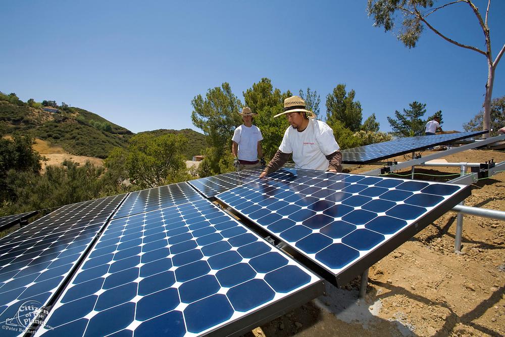 Green workers install a residential grid-tied solar array on a hillside in Malibu, Installation by Martifer Solar USA, California, USA