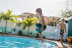 Little boy jumping into the pool, Mauritius