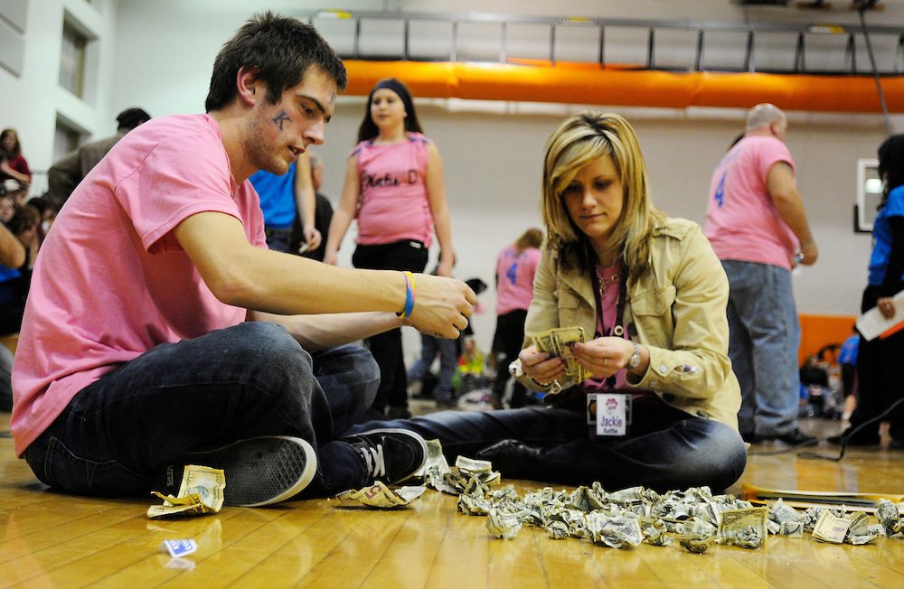 Matt Dixon | The Flint Journal..From Left, Alex Sieja, a senior at Fenton High and Jacklyn Pushman, a volunteer help sort money that was thrown onto the gym during a fundraiser for Katie Wyatt, a terminally ill eighth grader. The event aimed to raise money to help support Wyatt's medical bills in her fight against cancer.
