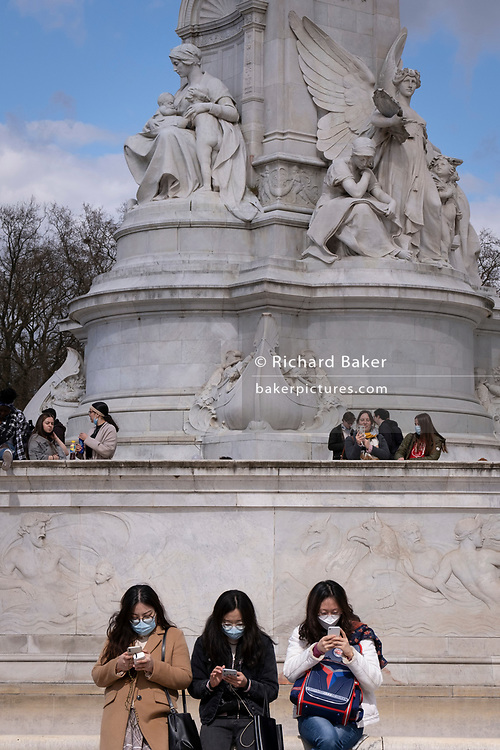On the day that the death of the Duke of Edinburgh was announced, three Asian visitors at the foot of the Victoria Memorial, opposite Buckingham Palace, pause to check and send messages on their phones, on 9th April 2021, in London, England.