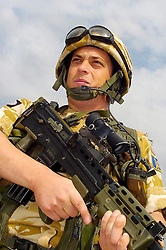 A British soldier, from the Muliti National Division in Kevlar helmet and desert camouflage stand guard with an SA80 and SUSAT at Basra Air Station during Op Telic Iraq 2005