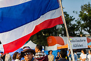 01 JANUARY 2014 - BANGKOK, THAILAND:  A man waits for Buddhist monks while he stands under a Thai flag before a merit making ceremony. Thousands of anti-government protestors are camped out at Democracy Monument in central Bangkok protesting against the government of Yingluck Shinawatra. The protest leader, Suthep Thaugsuban, has called for residents of the Thai capital to rise up against Yingluck. He has promised to shut the city of 12 million down in his final push to overthrow the government. About 100 members of the Thailand's Buddhist clergy visited the protest site Wednesday morning for a special merit making ceremony for the protestors.    PHOTO BY JACK KURTZ