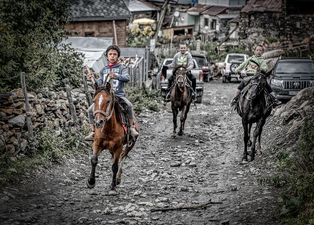 Children riding in the village of Ushguli in Georgia