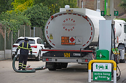 © Licensed to London News Pictures 28/09/2021.<br /> Mottingham, UK, A tanker driver working. A tanker has just delivered fuel to Mottingham BP station in South East London. Within minutes of the tanker arriving motorists started to queue blocking roads. Chaos at the forecourts as people start to panic buy petrol. BP has started to ration petrol and diesel due to a shortage of truckers. Photo credit:Grant Falvey/LNP
