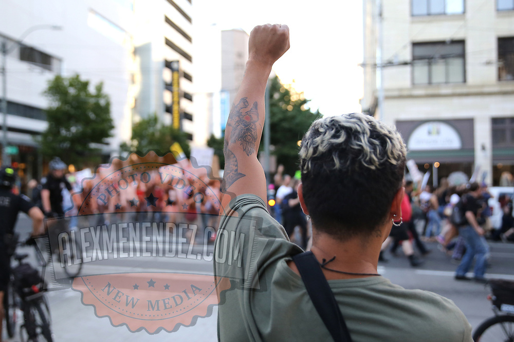 An observer raises his fist as protesters take part in a Black Lives Matter march, Saturday, August 26, 2017, in Seattle, Washington. Several thousand people attended a downtown rally and then marched through the city to call attention to minority rights and police brutality. (Alex Menendez via AP)