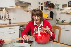 Senior woman seeking recipe on digital tablet for cake, Munich, Bavaria, Germany
