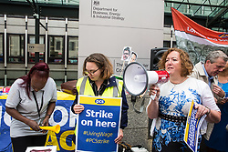 London, UK. 15 July, 2019. Fran Heathcote, President of the Public & Commercial Services Union (PCS), addresses catering and cleaning staff outsourced to work at the Department for Business, Energy and Industrial Strategy (BEIS) via contractors ISS World and Aramark on the picket line outside the Government department after walking out on an indefinite strike for the London Living Wage, terms and conditions comparable to the civil servants they work alongside and an end to outsourcing.