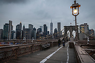 New York City, USA - March 19, 2020: Two cyclists ride over the Brooklyn Bridge at dusk. Due to the spread of coronavirus in New York City, traffic on the bridge was much less than normal.