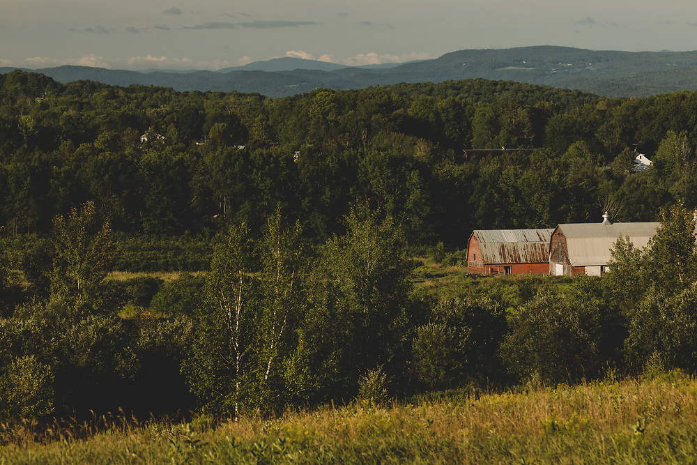 Morning sunlight shining upon the barns and hills of the rolling Vermont landscape.