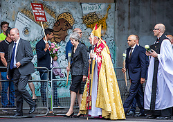 © Licensed to London News Pictures. 03/06/2018. London, UK. Prime Minister Theresa May (centre-left) and Bishop of Southwark Christopher Chessun (centre-right) walk from Southwark Cathedral to London Bridge to lay flowers and observe a minute's silence to mark the first anniversary of the London Bridge and Borough Market terror attack. Photo credit: Rob Pinney/LNP