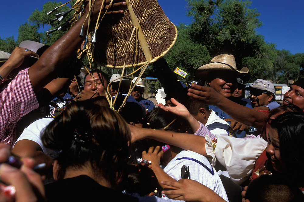 A basket filled with candy, maize and money is poured over an Apache girl at her Sunrise Dance, a first menstruation rite, on the San Carlos Apache Indian Reservation in Arizona, USA. This symbolises good luck and material wealth. The Sunrise Dance is the most important ceremony of the Apache Indians. It is held during the summer, within one year after the girl has had her first menstruation, and lasts for four days. The ceremony is an enactment of the Apache creation myth and during the rites the girl 'becomes' Changing Woman, a mythical female figure, and comes into possession of her healing powers. The rites are also supposed to prepare the girl for adulthood and to give her a long and healthy life without material wants.