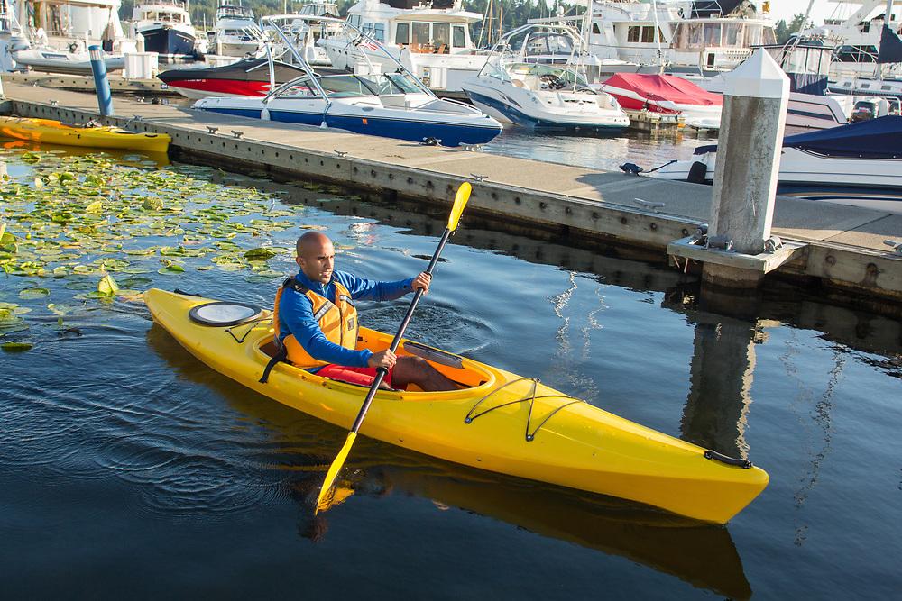 United States, Washington, Kirkland (near Seattle), Man kayaking in marina
