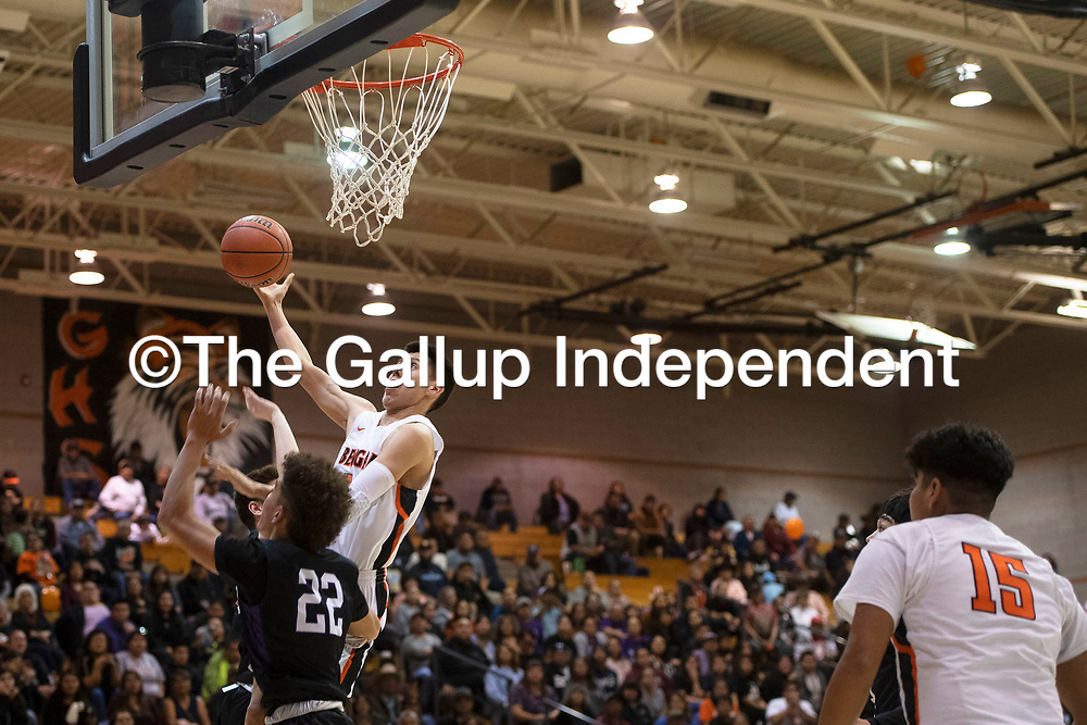 Gallup Bengal Quinn Atazhoon (24) drives to the basket for a layup as Miyamura Patriot Cael Stewart (22) defends Wednesday night at Gallup High School in Gallup. Gallup took the win 56-51.