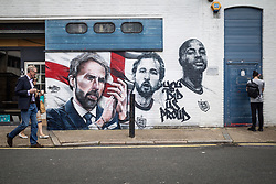 """© Licensed to London News Pictures. 14/07/2021. LONDON, UK.  People pass a mural by urban street artists MurWalls and commissioned by Sadiq Khan, Mayor of London, which has been unveiled in Vinegar Yard near London Bridge. Featuring the slogan """"You did us proud"""", the artwork celebrates the Engalnd football team's achievement in reaching the final of Euro 2020 and features an image of manager Gareth Southgate, captain Harry Kane and forward Raheem Sterling.  Photo credit: Stephen Chung/LNP"""