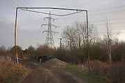 An electricity L6 pylon stands framed in height restriction poles on industrial wasteland at Barton Down, Canterbury, Kent
