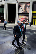 Businessmen walk along Fenchurch Street and pass a large face featured on the side of a temporary construction hoarding in the capitals financial district, on 14th May, in the City of London, England.