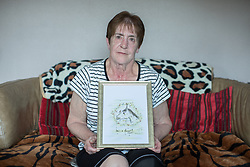 © Licensed to London News Pictures . 06/07/2017 . Manchester , UK . BARBARA DRANSFIELD poses with original artwork drawn for her by Charles Salvador . Artwork by convicted criminal  Charles Salvador (previously Charles Bronson) has been sold on behalf of Salvador to raise a £1,000 to support Barbara and Len Dransfield . Barbara , who has become friendly with Salvador , was brought the money and a card by Salvador's fiance , Paula Wiliamson . Barbara Dransfield was brutally assaulted by masked robbers as she sat at home in her wheelchair . She suffered extensive injuries to her face and body . Photo credit : Joel Goodman/LNP